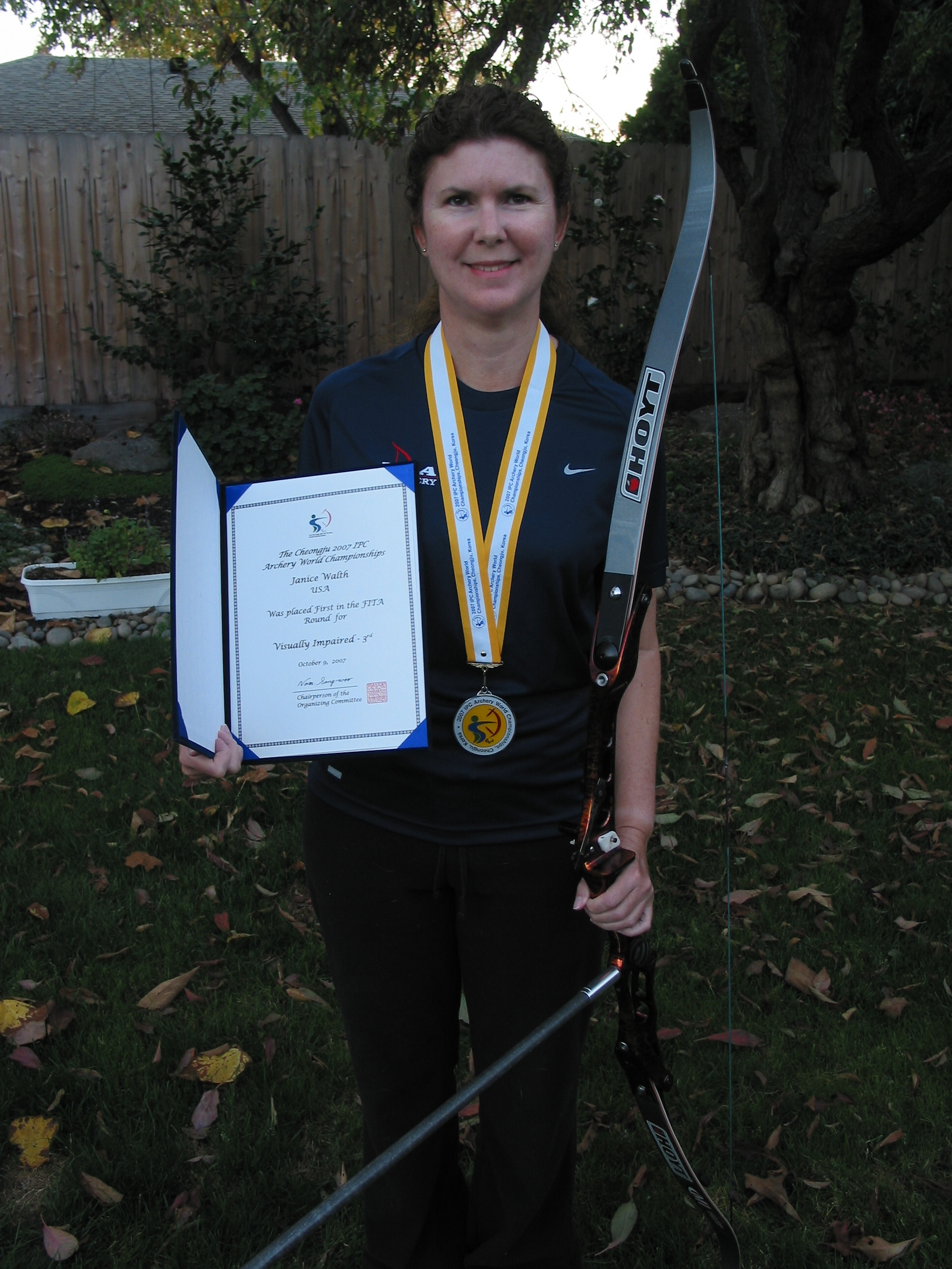 Janice Standing with silver medal around her neck. Her Hoyt bow is in her left hand and her award for the qualifier round is in her right hand