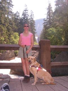 Janice standing with her guide dog, Liza, on a bridge overlooking Vernal Falls in Yosemite